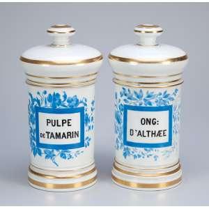 Par de potes de farmácia de porcelana branca, ornados por flores azuis e filetes dourados, <br />ambos com indicador de conteúdo. 26 cm de altura. França, séc. XIX.