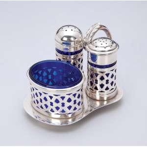 Saleiro, pimenteiro e mostardeiro de prata portuguesa e vidro azul cobalto. Acoplados em <br />suporte com alça recurva em forma de folha. Lisboa, teor 833 em uso a partir de 1938.