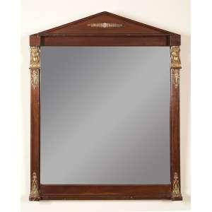 Espelho de cristal, em moldura de madeira estilo império, com apliques de figuras femininas de bronze. <br />73,5 cm de largura x 92 cm de altura. Séc. XIX.