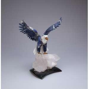 Objeto de adorno. Águia de asas abertas, esculpida em lápis-lazúli, sobre rochedo de cristal de rocha. 38 cm de altura. Acompanha certificado de autenticidade da Amsterdam Sauer, datado de 02/11/10.
