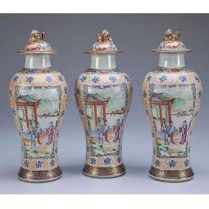 Garniture composta por três potiches com suas tampas de porcelana Cia das Índias, policromada e dourada, em forma de balaústre alongado. Bojo marmorizado com reservas em faces opostas contendo pintura de paisagem com figuras em atividades em primeiro plano; esmaltes da família rosa, pega da tampa em cão de fó. 28 cm de altura. China, Qing Qianlong (1736-1795).