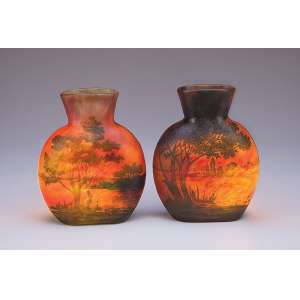 Raro par de vasos de pasta de vidro de Daum Nancy, decorados com paisagem lacustre em tons de <br />verde sobre fundo vermelho mesclado. 19,5 cm de altura. Assinados. França, séc. XX.