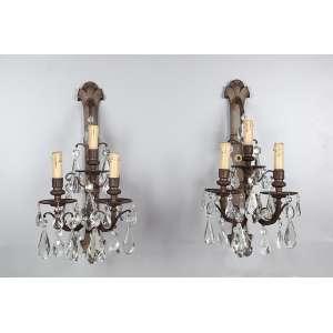 Par de arandelas para três lâmpadas cada, de bronze, ornamentadas por pingentes de cristal translúcido. <br />52 cm de altura. França, séc. XX.