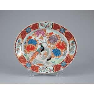 Travessa de porcelana policromada e dourada, ovalada, decoração no padrão Imari. <br />Apresenta no centro a fênix entre crisântemos. 40 x 33 cm. Japão, séc. XIX.