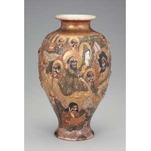 Vaso de porcelana Satsuma tipo mil caras em baixo relevo, policromado e dourado. Boca evasé com 10 cm de diâmetro x 31 cm de altura, sob a base ideogramas japoneses. Japão, séc. XIX.