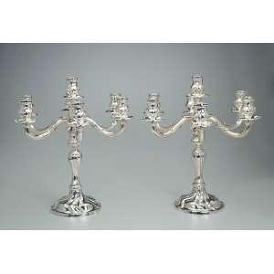 Par de elegantes candelabros de prata repuxada, para sete velas, base em campana e fuste em balaústre <br />com vincos ondeados; braços recurvos. 42 cm de altura. Marca da prata Sterling, teor 925. Europa, séc. XIX.