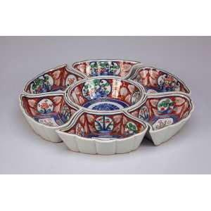 Petisqueira de porcelana policromada e dourada, decoração no padrão Imari, constituída de bowl central e seis recipientes laterais formando um círculo. 32 cm de diâmetro. China, séc. XIX.