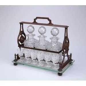 Tântalus de cristal de Baccarat, contendo três garrafas e 11 cálices para licor acoplados em estrutura de <br />bronze cinzelado. 35 x 21 x 30 cm de altura. França, séc. XIX. (apresenta pequenos bicados).