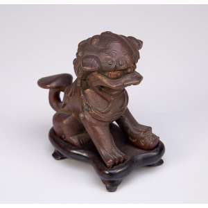 Cão de fó de bronze patinado sobre base de madeira; dimensões do bronze. <br />4,5 x 8,5 x 7,5 cm de altura. China, séc. XIX.
