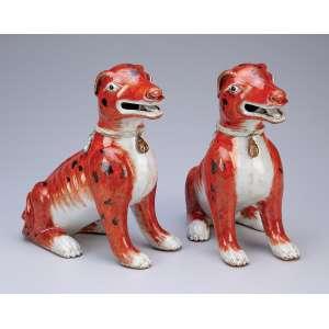 Dois cães de porcelana Cia das Índias, branca e rouge-de-fér, apresentam-se sentados. <br />19 cm de altura. China, séc. XIX.