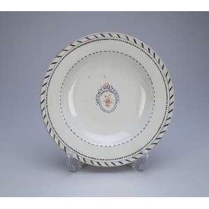 Prato de porcelana Cia das Índias, aba com filetes e perolados repetitivos. Na caldeira medalhão <br />floral com laçarote. 25 cm de diâmetro. China, séc. XVIII.