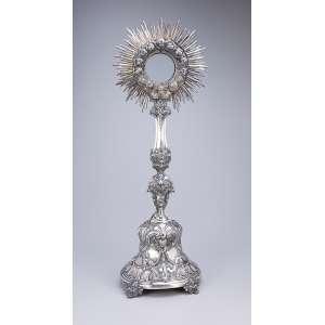 Grande ostensório de prata repuxada e cinzelada, decoração barroca, óculo envolto por <br />cabeças de anjo. 73 cm de altura. Brasil ou Portugal, séc. XVIII.