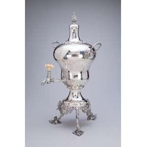 Refrescador de prata inglesa acoplado em base suspensa por três pés. <br />Apresenta brasão armorial. 55 cm de altura. Londres, 1845.