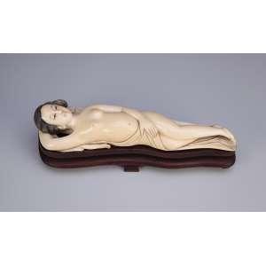 Escultura de marfim, figura feminina desnuda e deitada. Base de madeira. <br />20 cm de comprimento. Japão, séc. XIX.