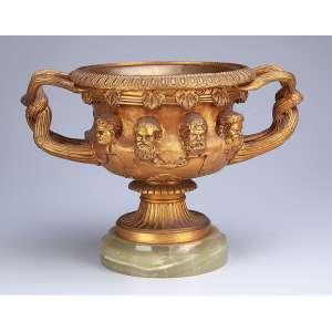 Centro de mesa em forma de taça, de bronze dourado, circular, com alças laterais entre laçadas; no bojo <br />bustos de figuras masculinas. Base de ônix. 20,5 cm de diâmetro x 21,5 cm de altura. Europa, séc. XIX.