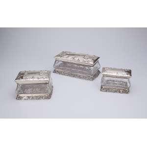 Conjunto de três caixas de cristal, retangulares, com tampas e bases de prata. <br />21 X 11 x 10 cm de altura a maior. França, circa 1900.