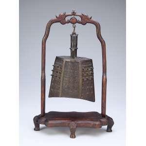 Gongo de bronze fixado em suporte de madeira. <br />38 cm de altura. China, séc. XVIII.
