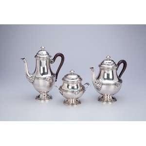 Serviço para chá e café de prata, composto de: bule para café, bule para chá com alças de madeira e açucareiro. 28 cm de altura, o bule para café. Contraste Cabeça de Mercúrio para a prata francesa de teor 950 em uso a partir de 1879.