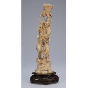 Escultura de marfim. Figura masculina sobre macaco e pássaro sobre sua cabeça. <br />Base de madeira. 41 cm de altura total. Assinada. Japão, séc. XIX.