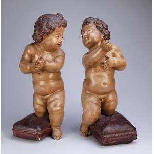 Par de cupidos, esculpidos em madeira patinada, olhos de vidro. <br />53 cm de altura. Brasil, séc. XIX.
