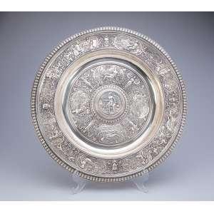 Medalhão de prata inglesa vitoriana, circular decorado com cenas neoclássicas em relevo. <br />47 cm de diâmetro. Birmingham, 1872.