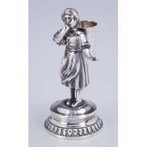 Paliteiro de prata, figura feminina portando cesto em seu costado. 11 cm de altura. <br />Contrastes prejudicados na leitura.