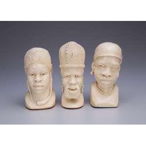 Lote de três bustos de africanos, de marfim, sendo duas figuras femininas e uma masculina. <br />14 cm de altura cada. África, séc. XX.