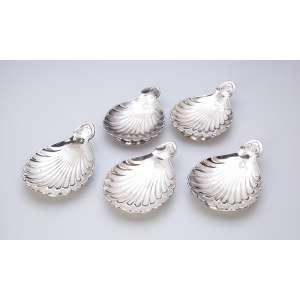 Conjunto de cinco covilhetes de prata, formato de conchas sobre base circular. <br />Contrastes prejudicados na leitura. 15 x 10 cm. Europa, séc. XX.