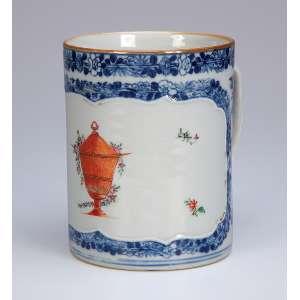 Caneca de porcelana Cia das Índias, decoração floral em azul sobre a coberta, reserva <br />com ânfora e pequenas flores em esmaltes da família rosa. 11 cm de diâmetro x 13,5 cm de altura. <br />China, Qing Qianlong (1736-1795).