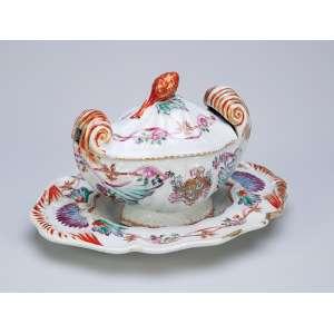 Açucareiro com présentoir de porcelana Cia das Índias, policromada e dourada. Na parte inferior do açucareiro e na aba do présentoir apresenta brasão de armas não identificado. Pega da tampa em pinha. 22,5 x 18 cm (o présentoir), 15,5 x 11,5 x 12 cm de altura, o açucareiro. China, Qing Jiaqing (1796-1820).