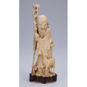 Escultura de marfim. Ancião com cajado e frutos em suas mãos e alce a seu lado. <br />21 cm de altura. Japão. séc. XIX.