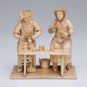 Grupo escultórico de marfim, casal de sapateiros, sentados frente a mesa de trabalho. <br />12,5 cm x 8 x 14 cm de altura. Europa, séc. XVIII.