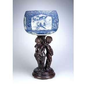 Escultura de bronze. Três crianças em círculo, encimadas por cachepô de porcelana azul e branca. <br />50 cm de altura, a escultura. 79 cm de altura total. França e China, séc. XIX.