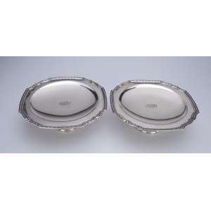 Par de pequenas fruteiras, elevadas, de prata lisa com borda recortada em godrons. <br />22,5cm X 8 cm de altura. Sob a base: Tiffany & CO. Sterling silver. Século XX.