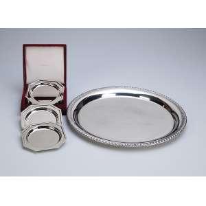 Bandeja redonda de metal prateado Sopil com 32 cm de diâmetro e quatro descansos para copo, <br />também de metal prateado. Acondicionados em estojo original. Brasil, séc. XX.