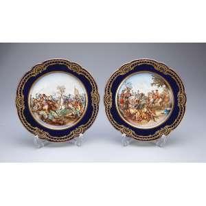 Par de pratos de porcelana de Sèvres, azul cobalto e douração. Plano com cenas de batalha. <br />24 cm de diâmetro. Marca da manufatura. França, séc. XX.