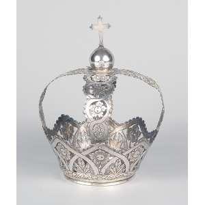 Coroa de prata com quatro hastes florais, encimada por esfera e cruz. 18 cm de altura. <br />Brasil, séc. XIX.