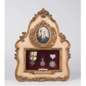 Placa emoldurada contendo o retrato pintado sobre pergaminho do Capitão Carlos José Dias Nascimento. <br />Assinado Lucas Teixeira e três medalhas. 25 x 33 cm.