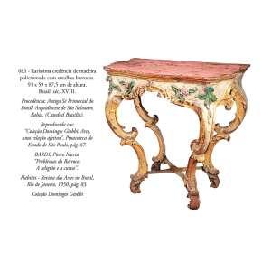 Raríssima credência de madeira policromada com entalhes barrocos. <br />91 x 59 x 87,5 cm de altura. Brasil, séc. XVIII. <br />Coleção Domingos Giobbi.
