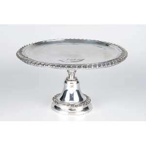 Salva esmoleira de prata repuxada e cinzelada, borda em godrons. 29 cm de diâmetro x 17 cm de altura. <br />Contrastes de Lisboa e do prateiro Manuel Troiano, citado em 1707. <br />Coleção Augusto Velloso.