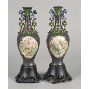 Par de vasos de prata e esmalte retratando paisagens orientais em reservas em faces opostas. <br />22 cm de altura, os vasos. Bases de madeira. Assinados em ideograma. <br />China, séc. XIX. (pequenos defeitos).