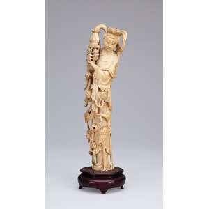 Escultura de marfim, gueixa com pote, flores e garça a seus pés. Base de madeira. <br />35 cm de altura. China, séc. XX.