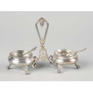 Saleiro e pimenteiro de prata guilhochada, duas cubas interligadas por alça suspensória. <br />16 x 13 cm. França, c. 1900.