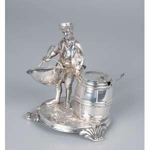 Paliteiro de prata repuxada e cinzelada. Homem com cesto ao lado de porta condimentos em forma de tonel. <br />Marca do teor 800. 12 cm de altura. Itália, séc. XIX.