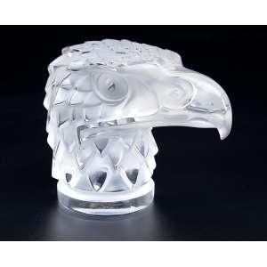 LALIQUE<br />Mascote / tampa para radiador. Tête de Aigle. Vidro branco moulé - pressé, patinado. 11 cm de altura.<br />Modelo criado em 1928, figurando no catálogo até 1932. <br />Reproduzido no catálogo do Raisonné, de Félix Marcilhac, na página 499.