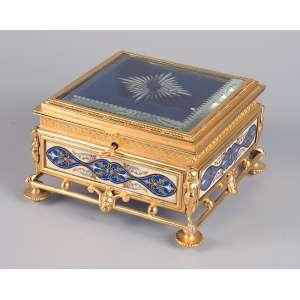Requintada caixa porta-jóias em metal dourado, tampa de cristal e laterais em placas <br />metálicas com esmalte champlevé. 17,5 x 17,5 cm de altura. França, séc. XIX.