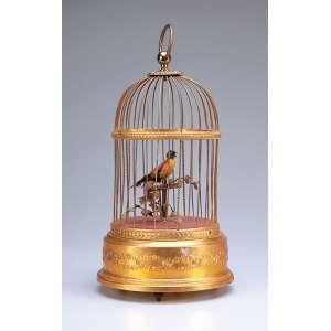 Gaiola de metal dourado, com pássaro cantante, através de mecanismo a corda. <br />17 cm de diâmetro x 32 cm de altura. França, séc. XX.