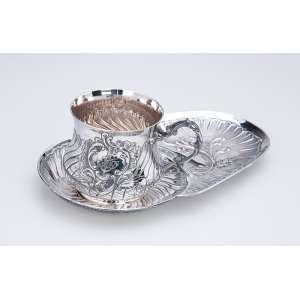 Xícara com pires alongado, de prata repuxada e cinzelada. 24 x 14,5 cm, o pires e 8 cm de altura, <br />a xícara. Contraste Cabeça de Minerva. França, c. 1900.
