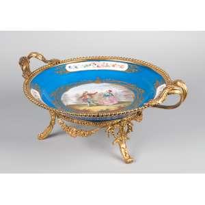 Fruteira de porcelana de Sèvres, azul royal, decorada com flores em três reservas e na caldeira <br />pintura de cena galante. Montantes de bronze dourado. Marcas da manufatura e do Chateau De Dreux. <br />32 cm de diâmetro x 18 cm de altura. França, séc. XIX.