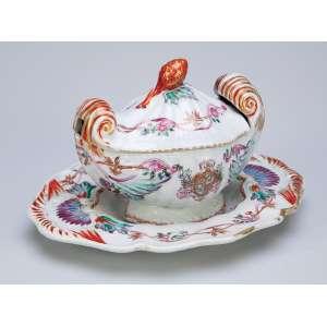 Açucareiro com présentoir de porcelana Cia das Índias, policromada e dourada. Apresenta brasão de armas não identificado. Pega da tampa em pinha. 22,5 x 18 cm (o présentoir), 15,5 x 11,5 x 12 cm de altura, <br />o açucareiro. China, Qing Jiaqing (1796-1820).